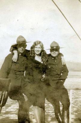 [Two Mounties and an unknown woman posing while sitting on a fence]