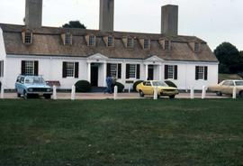 Building with three chimneys and three cars parked out front