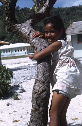 Girl hugging a tree on a white sandy beach]