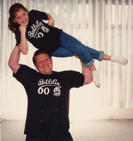 Robert Edel lifting young girl above his head, both wearing 'Bulletin 60' t-shirts