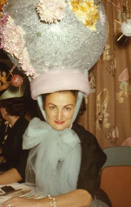 Phyliss Snider sitting at a table wearing a large unusual hat which looks like a blue globe with ...