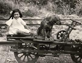 Little girl and dog on hand powered rail car