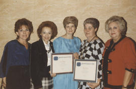 Five women, two holding certificates