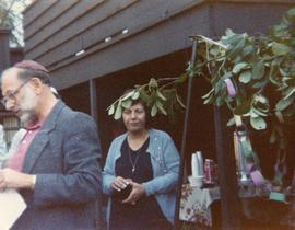 Unidentified man and woman standing near sukkah