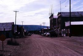 Dirt road in Dawson City with buildings on either side, one of them a hotel