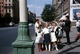 Group of children walking through the city under adult supervision