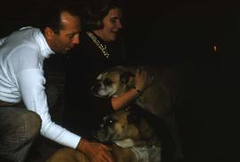 Unknown man and woman playing with two of the Snider's dogs