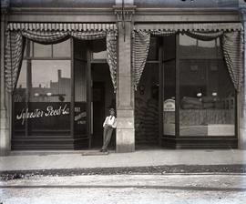 [Unidentified man standing in front of the Sylvester Feed Co. store]