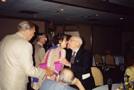 [Dr. Irving Snider leaning in to speak with an unknown woman and an unknown man is standing behin...