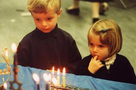 [Unidentified boy and girl looking at the Chanukah candles]