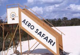 "Orange movable stairs with a logo and the words ""Aero Safari"" on the side"