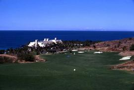 Golf course with a white building and the ocean in the background