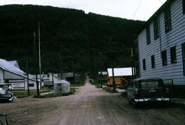Dirt road in Dawson City with buildings on either side, one of them a community hall