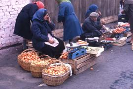 Group of women and a man selling vegetables among other food on the side of a street]