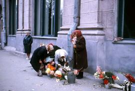 Group of women with headscarves situated on the street handling various arrangements of flowers i...