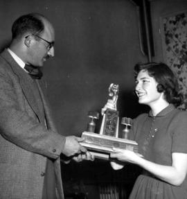 Young woman receiving trophy