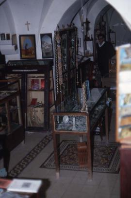 Interior of a store, with artwork, crucifixes, and bead [jewelry]