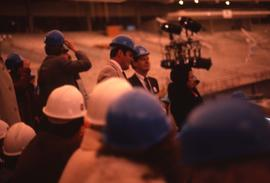 Group of unknown people wearing blue and white hard hats in what appears to be a stadium, probabl...