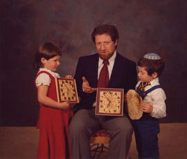Robert Edel with two children, holding two matzah clocks