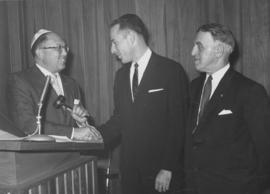 Three men at podium, 'A First in Vancouver'