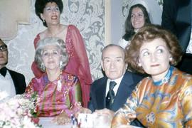 Harry Nemetz and Phyliss Snider sitting next to Bessie Karasov and an unknown man at a table and two unknown women are standing