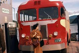 Phyliss Snider standing next to a red bus at a ferry station, part of Dawson City, Yukon