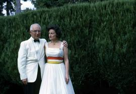 Dr. Irving and Phyliss Snider posing for the camera next to a hedge
