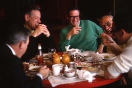 Five unknown men sitting around a table eating