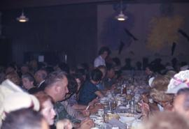 Group of unknown people sitting at long tables