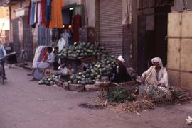 Unidentified man sitting next to a pile of watermelons