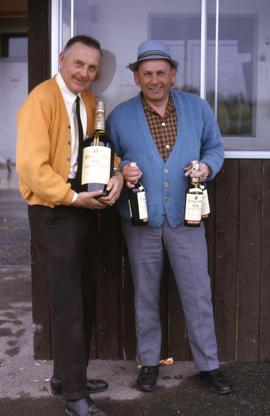 Two unknown men posing for the camera holding bottles of liquor