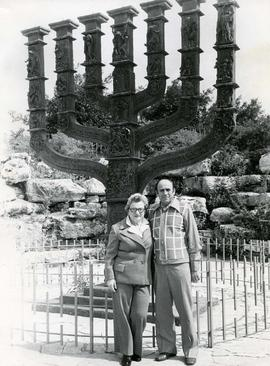 [Ben and Esther Dayson posing in front of a large menorah]