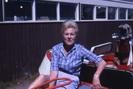Unknown woman sitting on a red golf cart