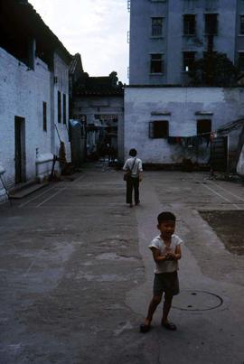 Boy standing in an open courtyard