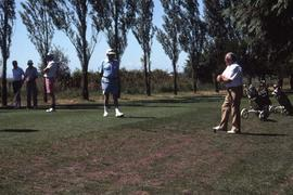 Five unknown men playing golf