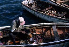 Man sitting in a boat shucking conch shells