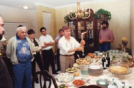 Adult - Shalom Kalfon [- group of people standing around food table]