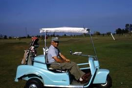 Dr. Irving Snider facing the camera while sitting in a light blue golf cart