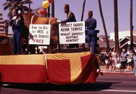 Three Shriners on a parade float with two signs