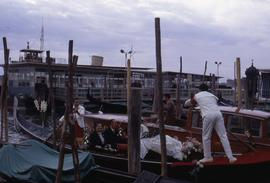 People sitting in a gondola with gondoliers standing on either end with wooden posts in the foreg...