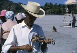 Unknown man playing a miniature violin on a beach