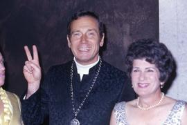 Unknown man giving a piece sign and an unknown woman standing next to him