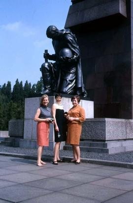 Three unidentified women standing in front of a monument
