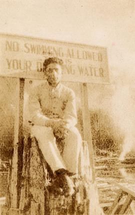 Member of the Seidelman family in front of a 'no swimming' sign