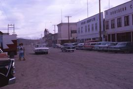 Unpaved street with parked cars and buildings in downtown Whitehorse