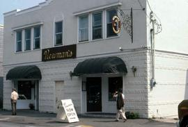 "White building with black awnings with a large sign that reads: ""Newman's"""