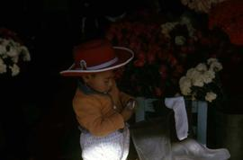 Young boy wearing a red cowboy hat with bouquets of flowers behind him
