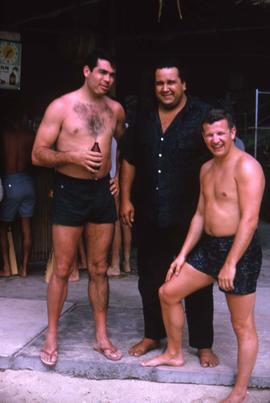 Three unknown men, two of which are in bathing suits