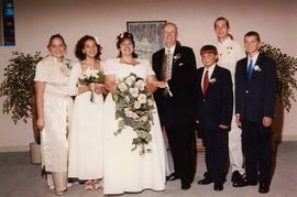 [Wedding photograph with an unknown bride and her wedding party posing for the camera]