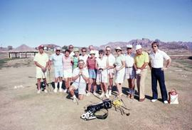 Group of unknown people holding golf clubs posing for the camera with a bag of golf clubs on the ...